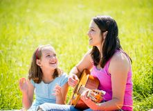 Mother playing guitar in nature Royalty Free Stock Images