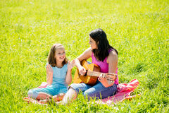 Mother playing guitar in nature Royalty Free Stock Image