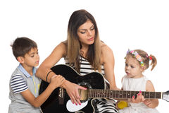 Mother playing guitar for their children Royalty Free Stock Image