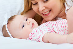 Mother playing with her baby on the bed. Mom smiles to her child.  stock photo