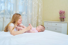 Mother playing with her baby on the bed. Mom smiles to her child Royalty Free Stock Images