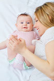 Mother playing with her baby on the bed. Mom smiles to her child Stock Image