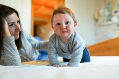Mother playing with her baby in the bedroom. happy family royalty free stock image