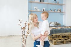 Mother playing with her baby in the bedroom. Happy loving family. Stock Photo