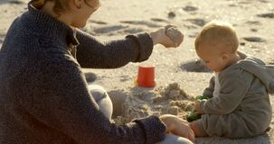 Mother playing with her baby boy in the beach 4k stock video footage