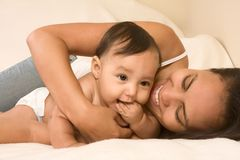 Mother playing with her baby boy son on bed Stock Photo