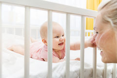 Mother playing with her baby in crib and having fun together. Mother playing with her infant baby in crib and having fun together Royalty Free Stock Photo