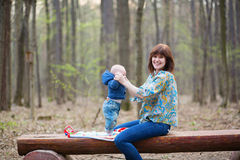 Mother playing with her baby in forest Stock Images