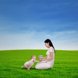 Mother playing with her baby in spring green field Royalty Free Stock Images