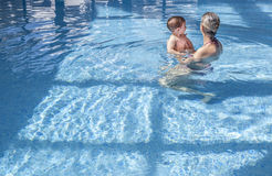 Mother playing with her baby at swimming pool indoor. Kids learn to swim during family vacation stock image