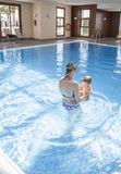 Mother playing with her baby at swimming pool indoor. Kids learn to swim during family vacation stock photo