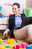 Mother playing with her child and checking e-mail Stock Image
