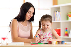 Mother playing with her child daughter, drawing together. Mother playing with her child girl, drawing together stock photos