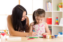 Mother playing with her child daughter, drawing together. Mother playing with her little daughter, drawing together Stock Photos