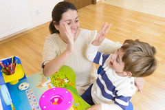 Mother playing with her child and encouraging him. Mother playing with her child some creativity game and encouraging him Stock Photo