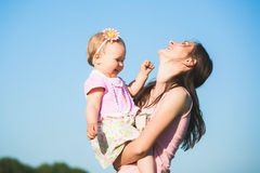 Mother playing with her child outside on sunny warm day stock image