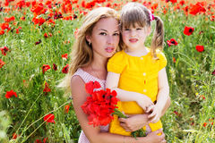 Mother playing with her child in poppy field Stock Photos