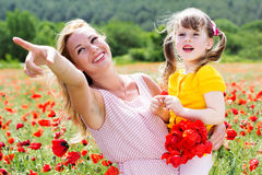 Mother playing with her child in poppy field Stock Images