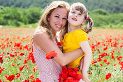 Mother playing with her child in poppy field Royalty Free Stock Photos