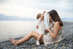 Mother playing with her daughter on the beach.  Stock Images