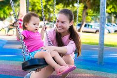 Mother playing with her daughter at the park. Pushing her child on the swing. royalty free stock images