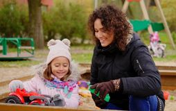 Mother playing with her daughter in a sandbox.  Royalty Free Stock Photos