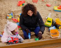 Mother playing with her daughter in a sandbox.  Royalty Free Stock Photo