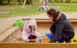 Mother playing with her daughter in a sandbox.  Stock Photography