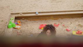 Mother playing with her daughter in a sandbox.  stock footage