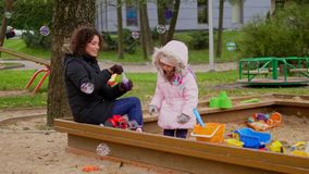 Mother playing with her daughter in a sandbox.  stock video
