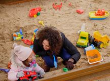 Mother playing with her daughter in a sandbox.  Royalty Free Stock Images