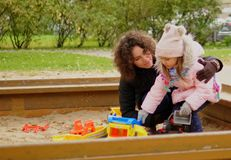 Mother playing with her daughter in a sandbox.  Stock Images