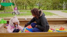 Mother playing with her daughter in a sandbox.  stock video footage