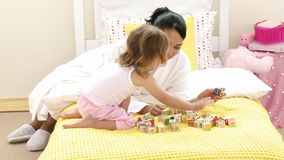 Mother playing with her daughters toy cubes in bedroom stock video