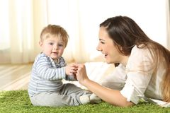 Mother playing with her kid that looks at camera. On the floor at home Royalty Free Stock Photos
