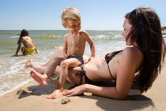 Mother playing with her kids on the beach. Young family enjoying their summer vacation at sea resort Stock Photos