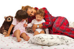 Mother playing with her kids in bed Stock Photo