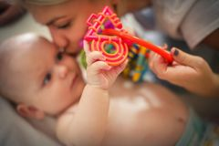 Mother playing with her little baby boy holding toy and kissing. stock images