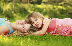 Mother playing with her little daughter on the grass Royalty Free Stock Image