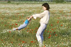 Mother playing with her son. In flowers Stock Photos