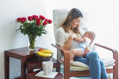 Mother, playing with her toddler boy, breastfeeding him. Mother, playing with her toddler boy at home in rocking chair, smiling, breastfeeding royalty free stock photos