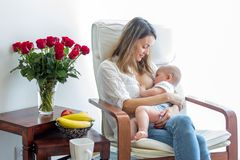 Mother, playing with her toddler boy, breastfeeding him. Mother, playing with her toddler boy at home in rocking chair, smiling, breastfeeding stock photography