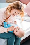 Mother playing with laughing little child. While sitting on bed at home royalty free stock photo