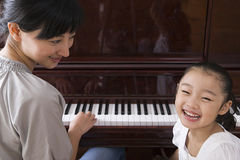 Mother playing the piano for her daughter Stock Photo