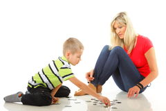 Mother playing puzzle together with her son Stock Photos