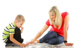 Mother playing puzzle together with her son Stock Photography