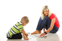 Mother playing puzzle together with her son Stock Image