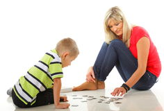 Mother playing puzzle together with her son Royalty Free Stock Photos