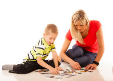 Mother playing puzzle toy with her son Stock Photos