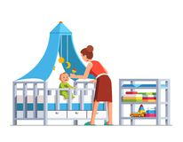 Mom playing rattle to baby son sitting in crib bed. Mother playing rattle to little baby son toddler sitting in crib bed or cot. Woman babysitter looking after Stock Image